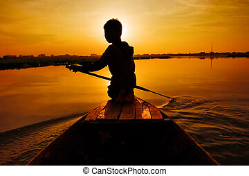 Sunset boat ride - Silhouette of boy paddling boat at sunset