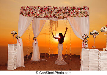 Sunset. bride silhouette. Wedding ceremony arch with flower...
