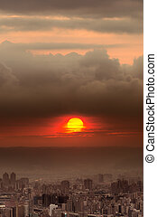 Sunset city scenery with red sun over buildings and clouds ...