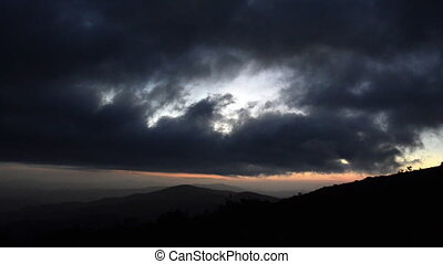 Sunset Clouds over grassy ridge - As night falls over the...