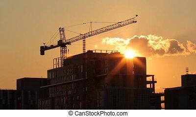 Sunset crane. - Tower crane and condominium at sunset. Real...