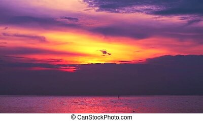 sunset dark purple on red cloud moving down on the sea and orange sky background