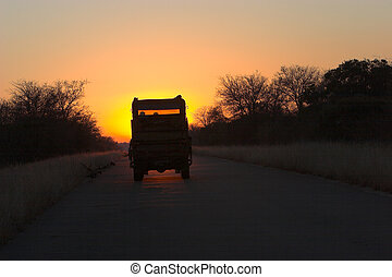 Sunset drive - Safari vechicle driving romanticly into...