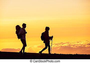 Sunset Hikers - Silhouettes of two hikers with backpacks...