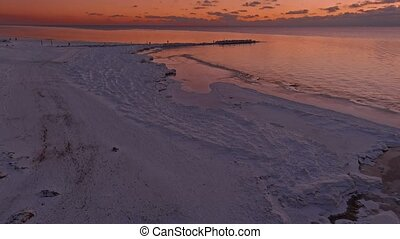 Sunset in a calm sea with frozen seashore. Shot from drone