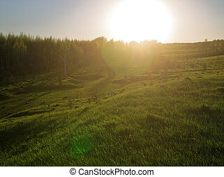 sunset in a field on the outskirts of the village