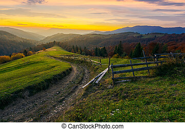 sunset in autumn mountains. winding country road through...
