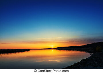 sunset in blue sky over river