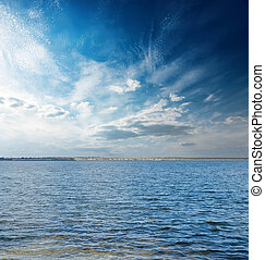 sunset in blue sky with clouds over river