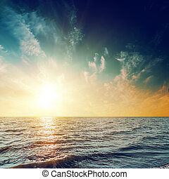 sunset in dark sky over sea with reflections