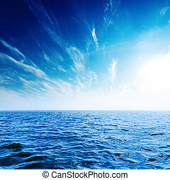 sunset in deep blue sky with clouds over sea