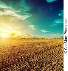 sunset in dramatic sky over plowed field