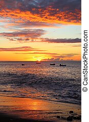 Guadeloupe black sand beach. Caribbean vacation landscape. Sunset at Plage Caraibe beach in Pointe Noire.
