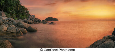 Sunset in phuket beach with rock