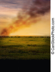Sunset in steppe with smoke defocused