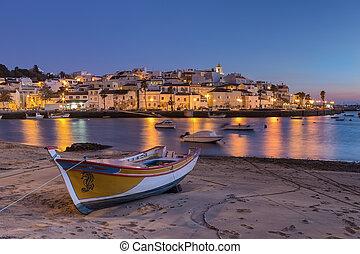 Sunset in the bay of Ferragudo, Portimao. Fishing boat on the shore.
