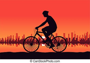 Sunset in the city with person driving on a bicycle