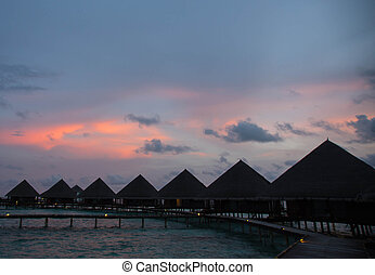 Sunset in the Maldives with a view of the ocean, sky and bungalows