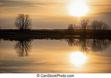 Sunset in the meadow. The sun, sky and trees are reflected in the river. Spring flood