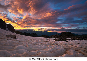 Sunset in the mountains. Beautiful cloudscape. Silhouette of mountain range with snow dunes reflecting sunset colours.