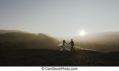 Sunset in the mountains. Beautiful young bride and fiance walks in the sunset on the background of the river and the forest. Conception of wedding day. Romantic evening