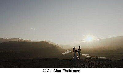 Sunset in the mountains. Beautiful young couple hugging in the sunset on the background of the river and the forest. Conception of wedding day