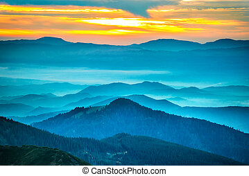 Sunset in the mountains. Dramatic colorful clouds over blue hills