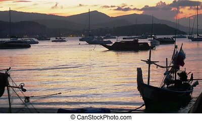 Sunset in the peaceful fishing port. Fishing boats anchored...