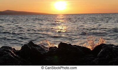 Sunset in the sea. Waves crush on black stones and splashes shine in sunlight
