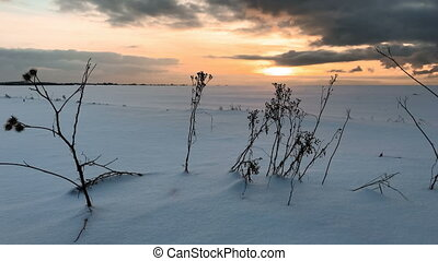 Sunset in the winter snow field. Time lapse video.