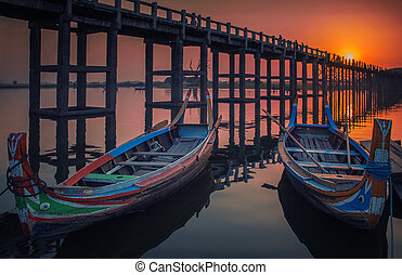 Sunset in U Bein bridge with vintage boat