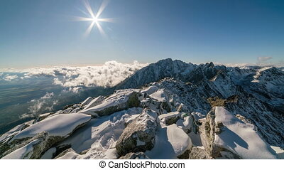 Sunset in winter snowy mountains above clouds, rocks and snow time lapse