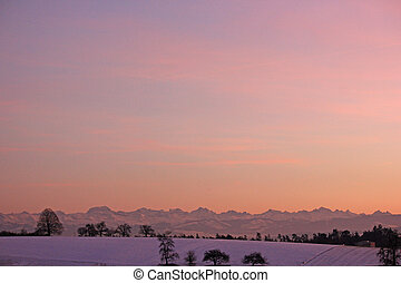 sunset in winter with mountains in the background