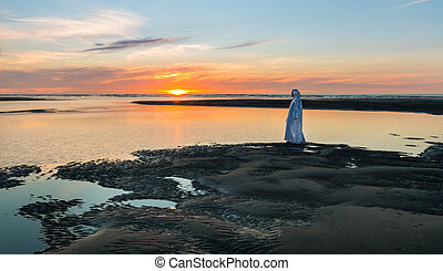 Sunset Jesus Christ - Jesus Christ walking at a beach as the...