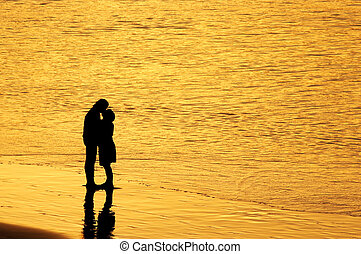 Sunset kiss - Couple kissing at sunset on the beach