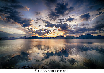 Sunset landscape, lake with beautiful clouds in the background.