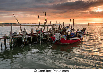 Sunset landscape of artisanal fishing boats in the old wooden pier