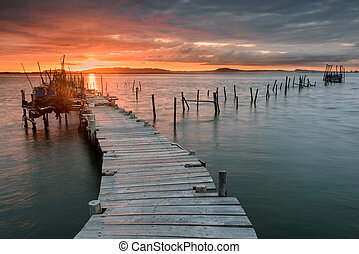 Sunset landscape of artisanal fishing boats in the old wooden pier.