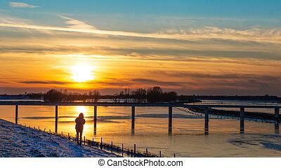 Sunset landscape with frozen floodplains in The Netherlands