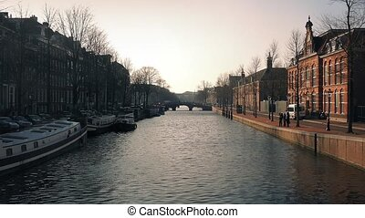 Sunset Light On Buildings By Canal - Scenic canal with...