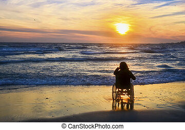 Sunset, makes sightseeing on the beach a woman on wheelchair