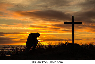 Beautiful sunset as man bows down to pray God before a cross.