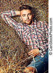 sunset man - Handsome young man lying in haystack.