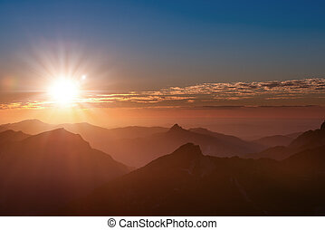 sunset mood on top of tirol mountain with peaks clouds and sun