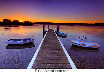 Sunset moorings and boat jetty in a little cove Australia - ...