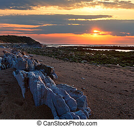 Sunset ocean view from stony beach