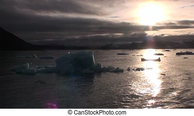 Sunset on a background of snowy icebergs of Arctic Ocean in Svalbard.