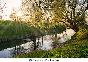 Sunset on a river and a reflecting water surface