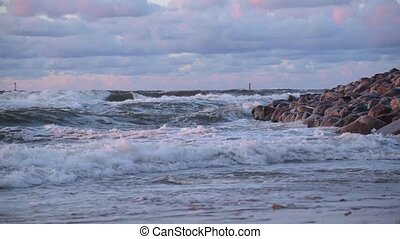 Sunset on a stormy sea. The Big Waves crash on the rocky shore.