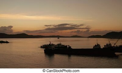 Sunset on a tropical island with a seaport. - Silhouettes of...